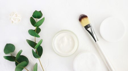 Jar of organic beauty product and application brush with fresh green leaves herbal bough, top view white background.